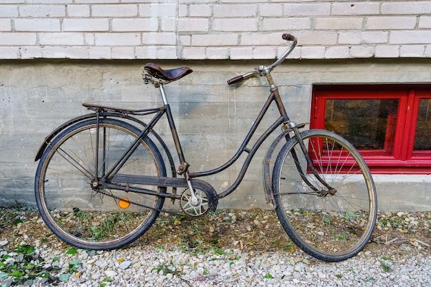 古い建物の壁に駐車していた古いさびた自転車。