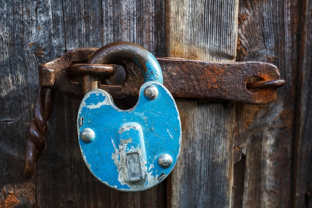 The old rusty blue lock is closed on the door of the door.