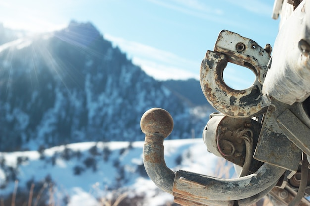Old rusty car hitch on a background of mountains