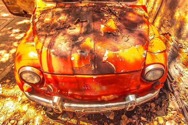 汚い壁の前に古い錆びた車