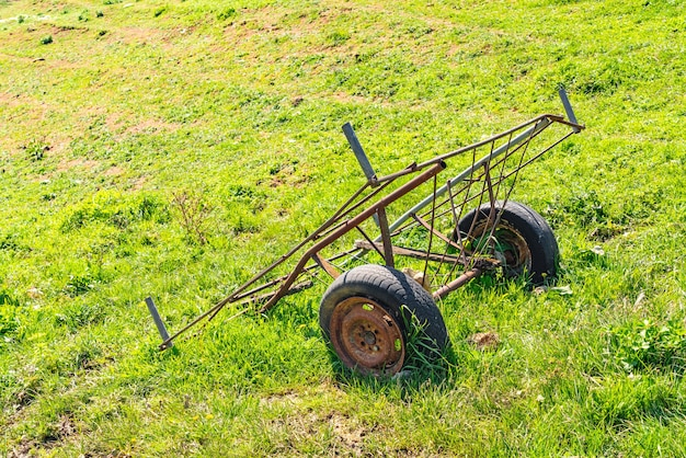 Старая ржавая тележка на поле