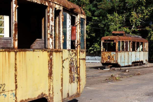 Old rusty destroyed tram wagons outdoors at sunny day.