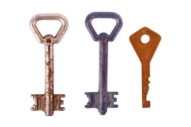 Old rusty door key isolated on white. three key set