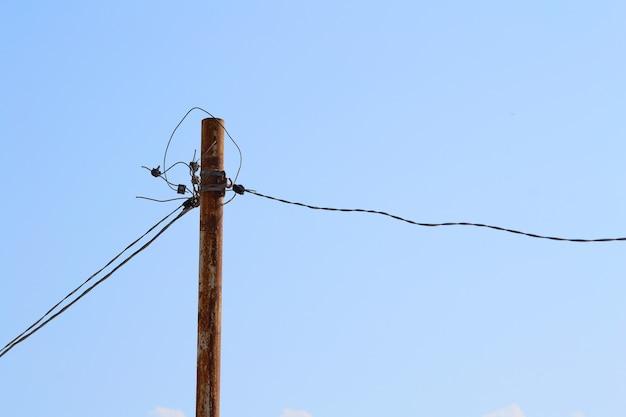 Старый ржавый электрический столб с проводами
