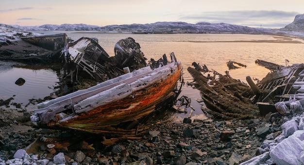船の墓場の海岸で嵐に見捨てられた古いさびた漁船 Premium写真