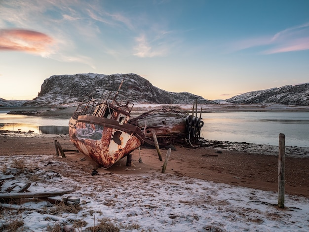 An old rusty fishing boat abandoned by a storm on the shore. graveyard of ships, old fishing village on the shore of the barents sea, the kola peninsula, teriberka, russia.