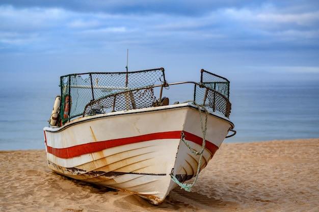 背後の海の景色を望む砂浜の古いさびた漁船