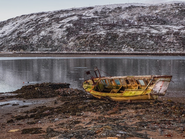 An old rusty fishing boat washed up on a sandy beach in the barents sea. authentic the north sea. pollution of the coastline. russia.