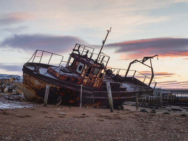 An old rusty fishing boat washed up on a sandy beach in the barents sea. authentic the north sea. russia.