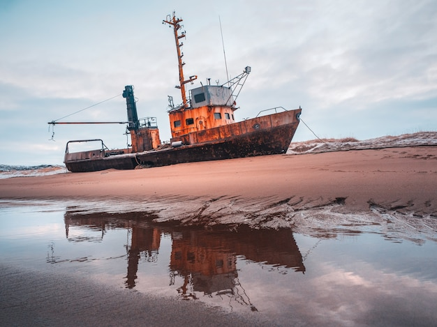 Old rusty fishing boat washed up on a sandy beach in the barents sea