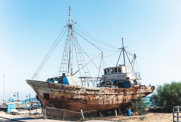 Old rusty fishing ship standing on land near sea.
