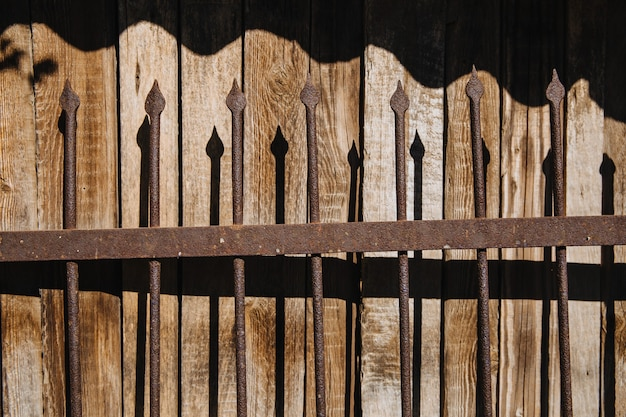 An old rusty forged fence with spikes behind the fence there is a wooden background