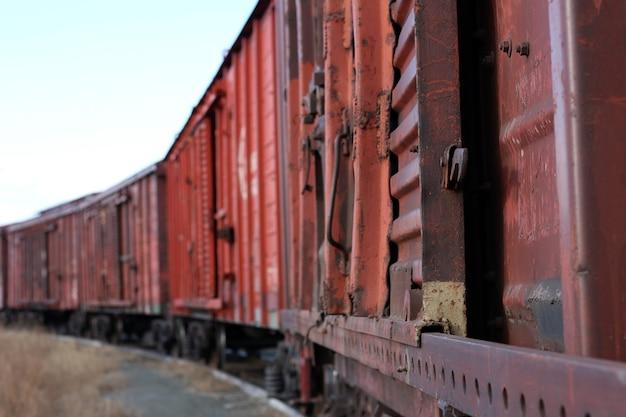 Старый ржавый грузовой поезд стоит на рельсах на переднем плане, резкость еще более размыта от середины вагона до конца поезда.