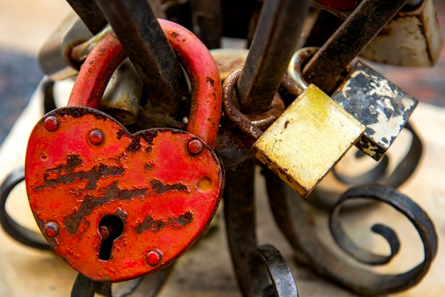 Old rusty heart shaped locks on a wrought iron railing