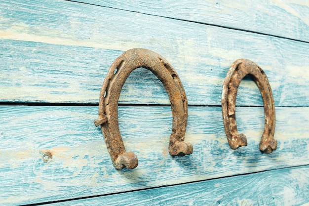 Old rusty horseshoes on wooden board