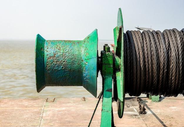 古いさびた鉄のアンカーケーブルまたは船のロープスプールが川のクローズアップビュー