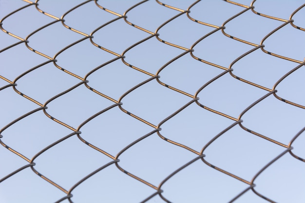 Old and rusty iron net wrapped on blue sky background.