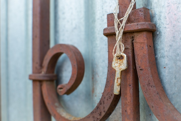 Old rusty key hangs on the old fence. lost keys and opportunities concept. close up with copy space for text.