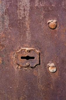 Старая ржавая замочная скважина в двери гаража с большими заклепками