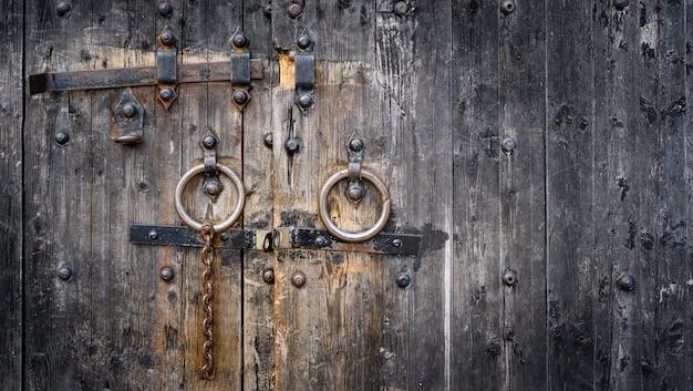 アンティークの木製のドアゲートの古いさびたロックボルト。