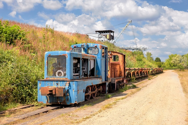 Old rusty locomotive with a row of coal vagons and  bucket chain excavator