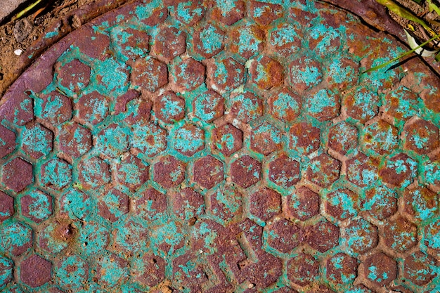 Old rusty manhole with traces of blue peeling paint.