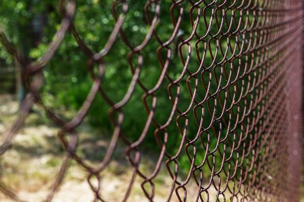 Старая ржавая сетка размыта. красочный узор. металлические ржавые заборы.