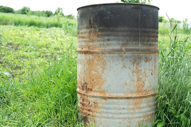 고철과 쓰레기 소각을 위해 풀밭에 가까이 있는 시골 집 뒤뜰에 있는 오래된 녹슨 금속 배럴과 스토브
