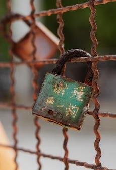 울타리에 닫힌 오래 된 녹슨 금속 자물쇠