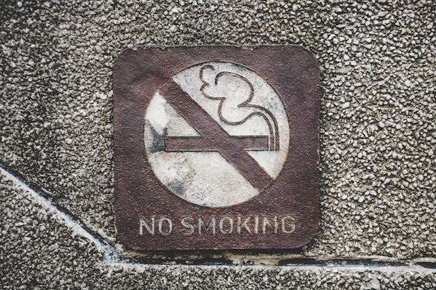 Old rusty metal no smoking allowed sign on dirty pebbles stone wall texture in public place