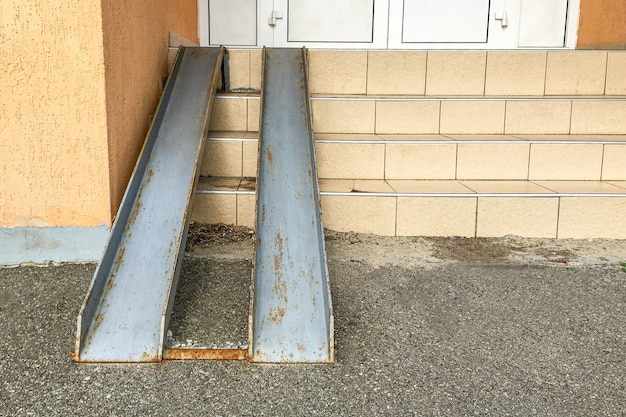 Old rusty metal ramp for entry of wheelchairs and baby carriage, over steps.