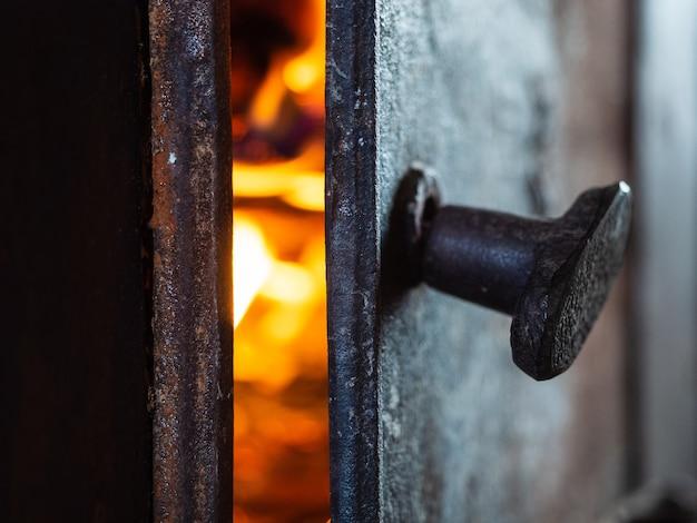 ドアが開いている古いさびた金属ストーブ