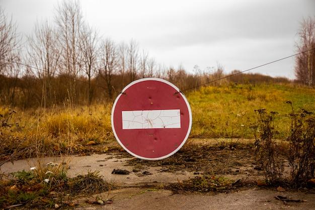 フィールドの古い放棄された道路に古いさびたエントリサインはありません。閉じる
