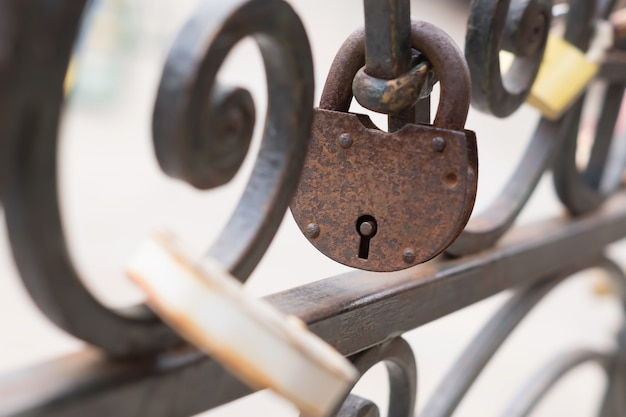 Old rusty padlock on iron fence. selective focus.