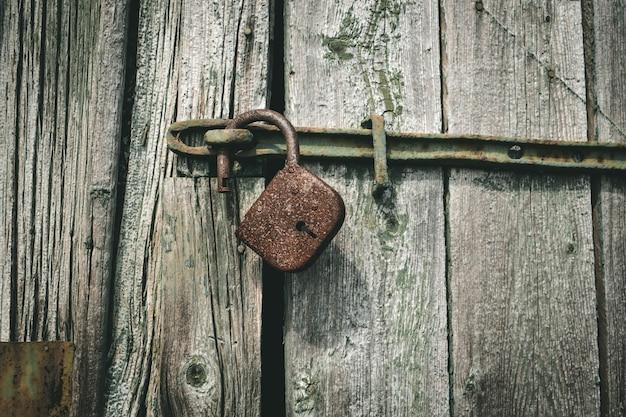 木製のドアに古いさびた南京錠。ヴィンテージロックを開きます。安全保護の概念。南京錠を開けた