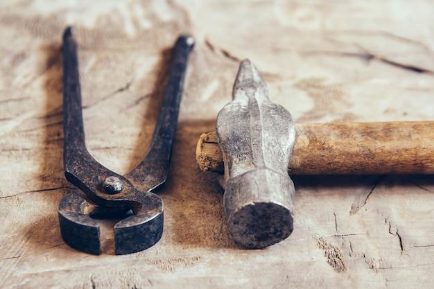古いさびたはさみと木製の背景にハンマー。物をつかんだり引っ張ったりするための道具。