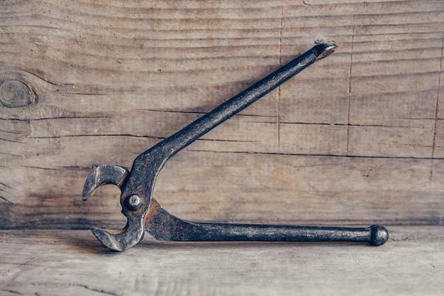 木製の背景に古いさびたはさみ。物をつかんだり引っ張ったりするための道具。