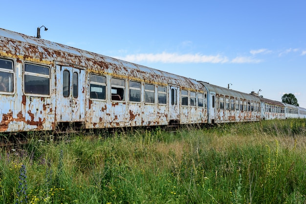 Old rusty railway wagon whit broken windows. old abandoned track, siding with dirty old trains. old railway tracks.