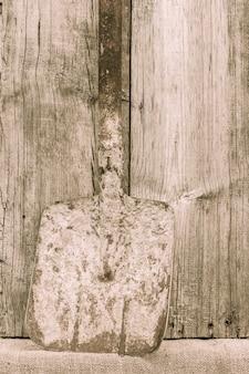 오래 된 녹슨 삽입니다. 국가 도구. 나무 배경에 소박한 악기, 도구 및 농기구. 빈티지 스타일