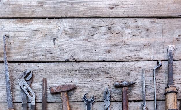 黒い木製のテーブルの上に横たわる古い、さびたツール。ハンマー、ノミ、弓のこ、金属レンチ。コピースペース