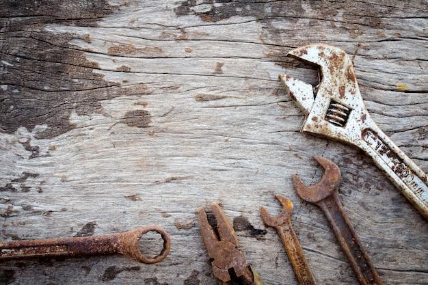 古い木材の背景に古いさびたツール。木製のレンチ。素朴なスタイル。上面図