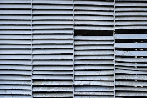 Старая ржавая вентиляционная решетка перед промышленным зданием