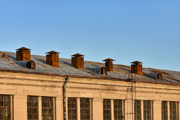 Old rusty ventilation pipes on the roof of a multistory building