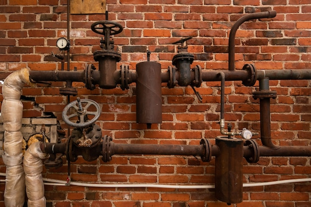 Old rusty water pipes with shutoff valves and sensors in an industrial building on a brick wall