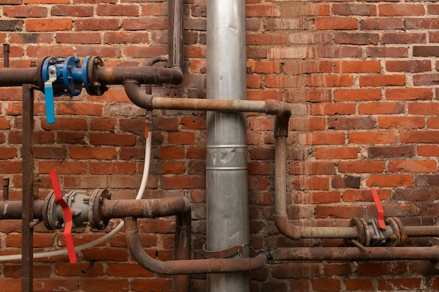 Old rusty water pipes with valves in an industrial building opposite a brick wall.