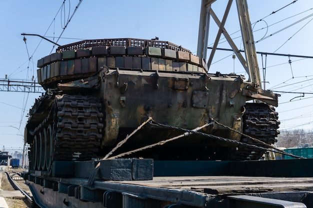 Old rysty tank with artisanal reactive armor on a railway flatcar