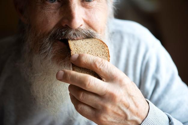 긴 회색 수염을 기른 슬픈 노인이 탁자에 앉아 빵을 먹고 있다