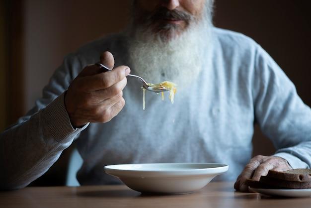 긴 회색 수염을 기른 슬픈 노인이 탁자 옆에 앉아 수프와 빵을 먹고 있다