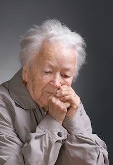 Старая грустная женщина на сером фоне