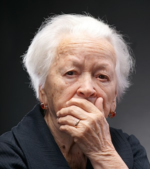 Старая грустная женщина позирует в студии на сером фоне